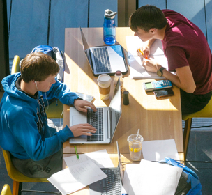 two male students sitting at a table and studying