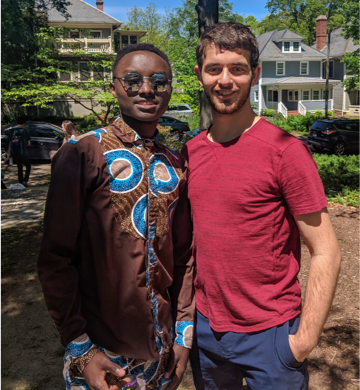 Duke undergraduate student Andrew Carlins posing with refugee Faustin