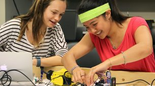 two female students building a robot together