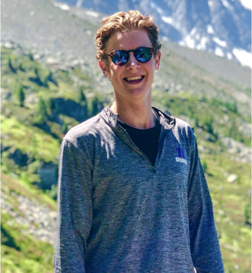 Duke undergraduate Edward Coles smiling with mountains behind him
