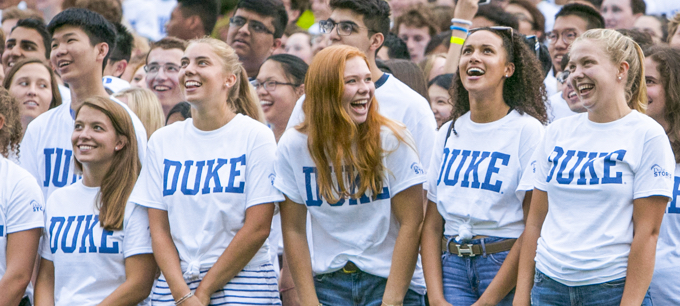 duke freshmen smiling and laughin with duke t-shirts in a crowd