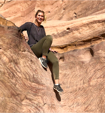 Duke undergraduate Claudia LaRose smiling while sitting on rocks in Petra
