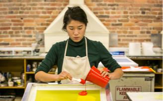 student pouring red liquid onto yellow paper in an art studio