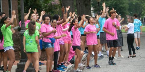 students in neon-colored tshirts shouting with their hands up