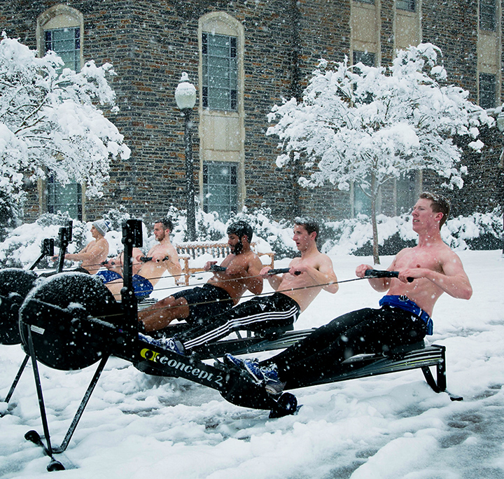 five shirtless male students using rowing machines outside in the winter snow