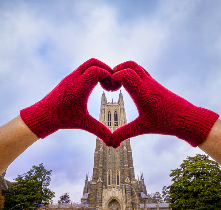 hands with red gloves making a heart over the Duke chapel