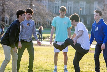 five students playing hacky sack