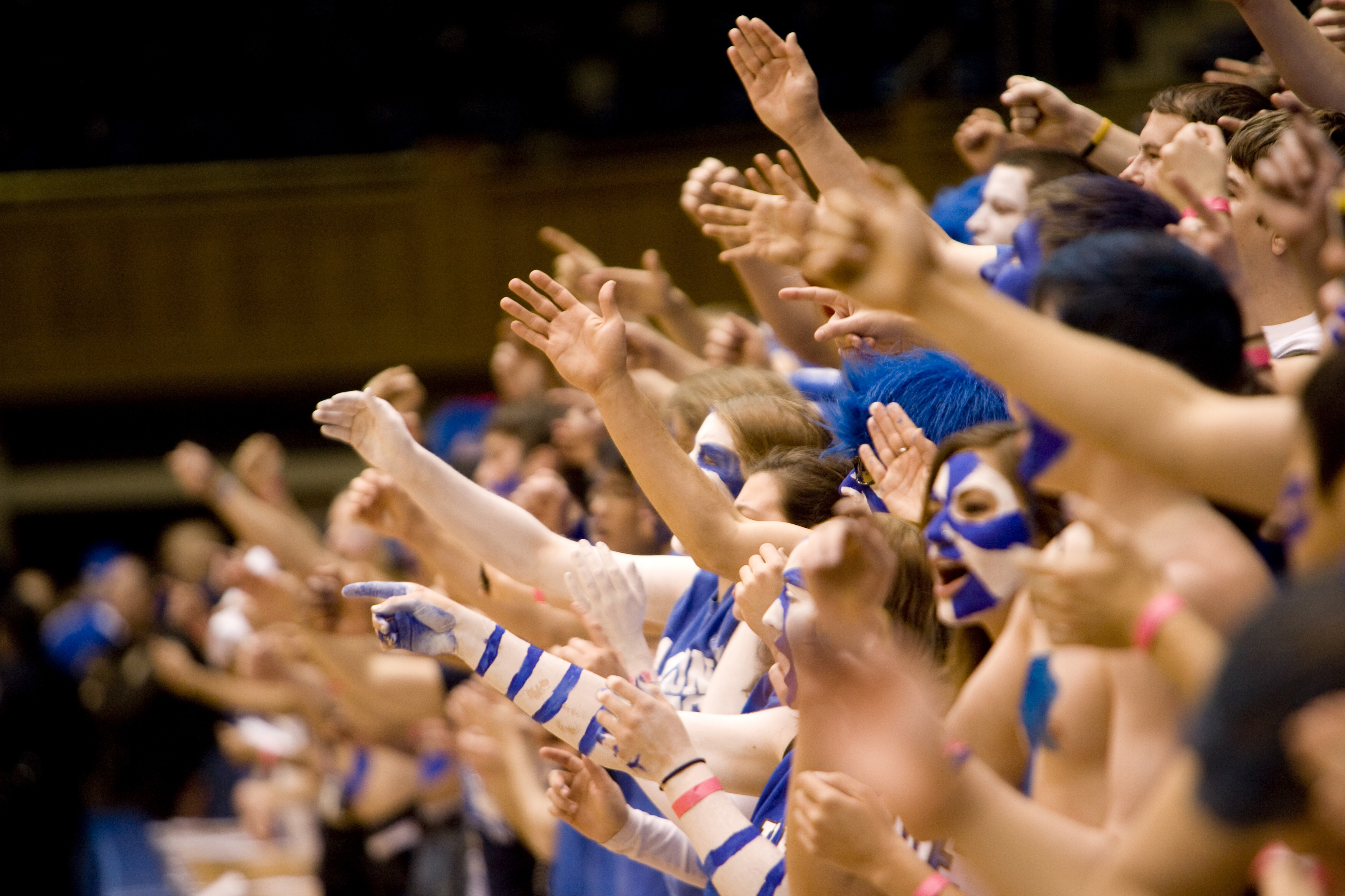 crowd of students in the stands, dressed in duke blue cheering and waving