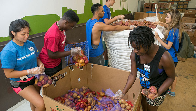 six students sorting food at a food bank