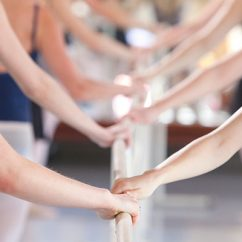 female students holding a ballet bar in a dance studio