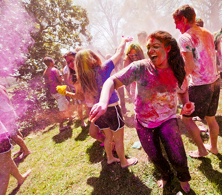 students covered in colorful powder laughing and playing holi on a field in the daytime