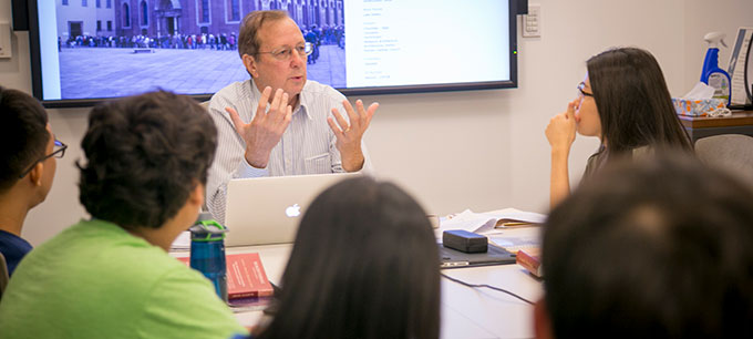 professor sitting behind computer explaining something with his hands in a classroom while students listen