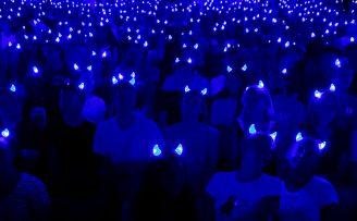 crowd of students in the dark wearing duke blue glowing devil horn headbands