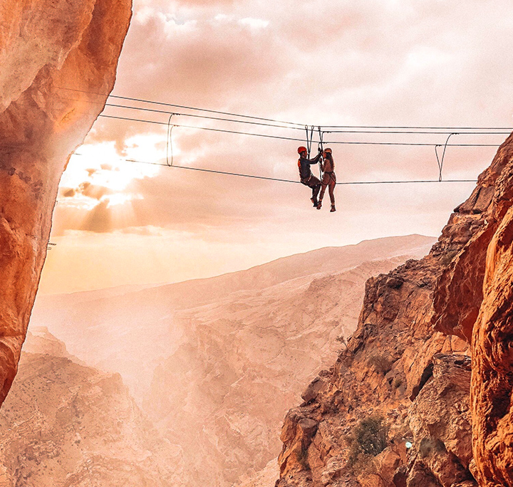 two students hanging on a zip line across two cliffs