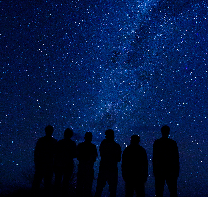silhouette of six students in front of a starry night sky