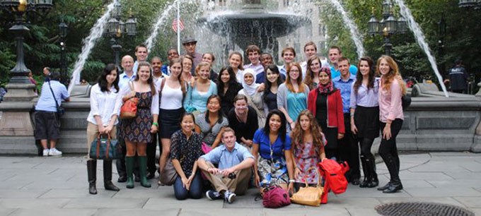 large group of students gathered around fountain in new york city