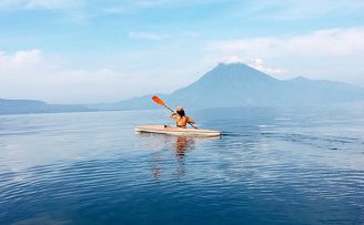 student kayaking in lake atitlan, guatemala with mountains in the background