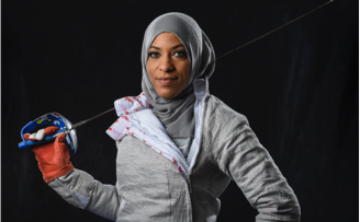 Ibtihaj Muhammad wearing olympic uniform, holding fencing sword