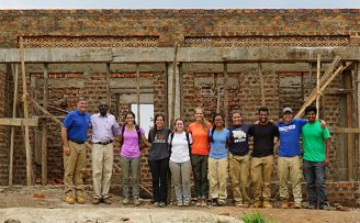 students and faculty posing together in front of a house being built