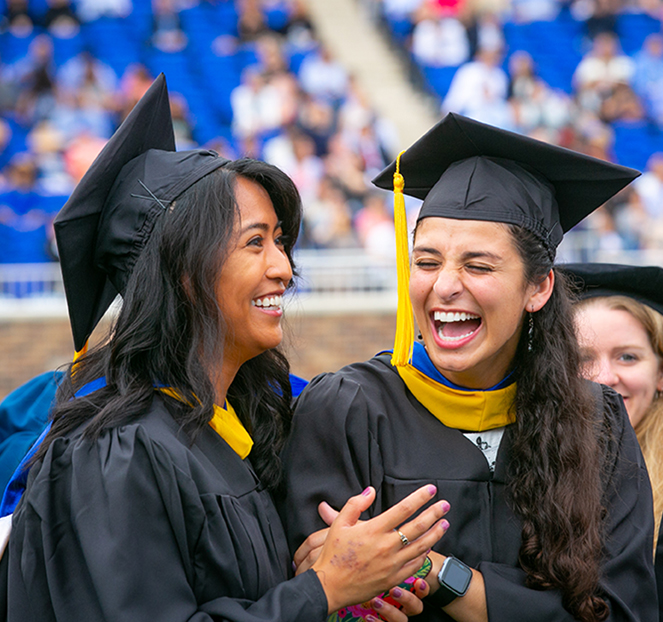 two female duke students in their caps and gowns laughing together at commencement