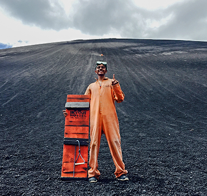 student in orange jumpsuit posing on volcanic ash