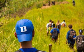 student hiking through tall grass