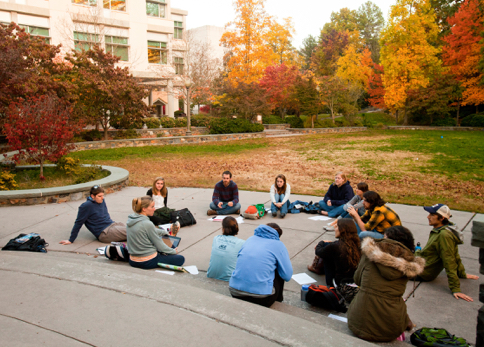 students sitting outside in a circle on a fall day