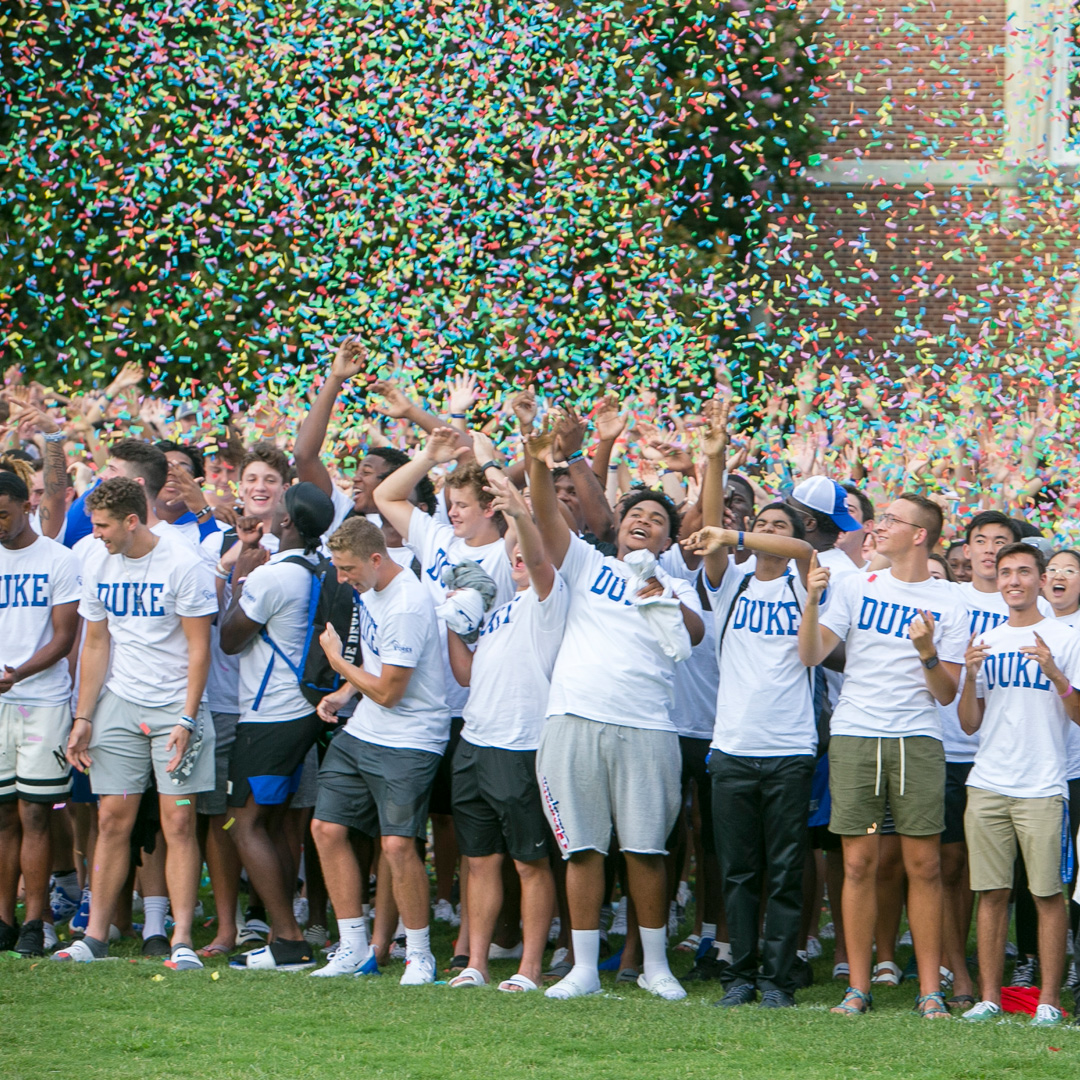First-year students raise their hands to touch confetti.