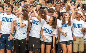 Image of students wearing Duke shirts and looking at confetti falling from the sky