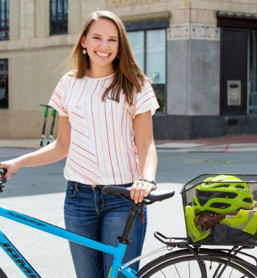 Samantha stands with her bike in Downtown Durham